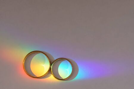 Background with two wedding rings with rainbow light. Stok Fotoğraf