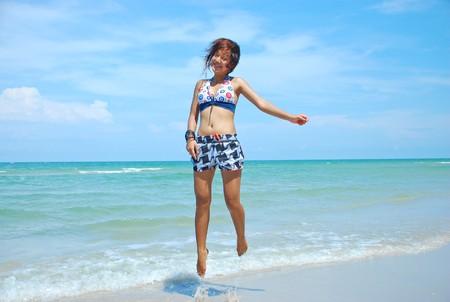 a woman jumps on sea Huahin beach Stock Photo