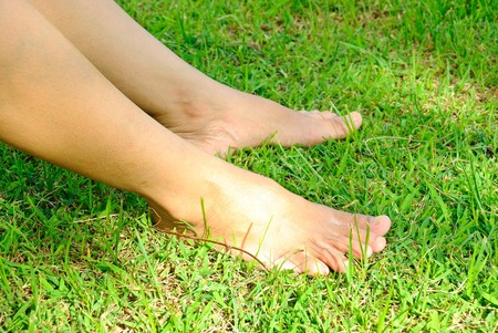 woman leg stands on the lawn