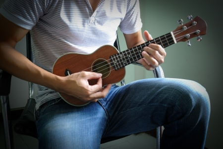 acoustic ukulele: man play ukulele Stock Photo