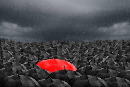 Colorful umbrella in mass of black umbrellas.