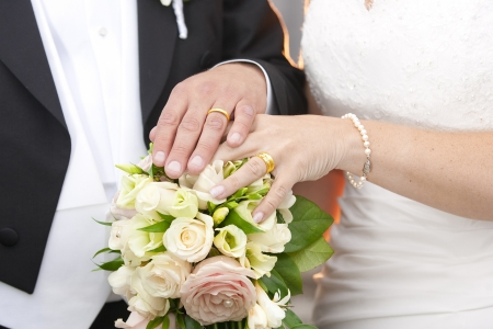 Newlywed couple holding hands on a bouquet Stock Photo - 14359113