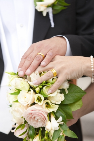 Newlywed couple holding hands on a bouquet