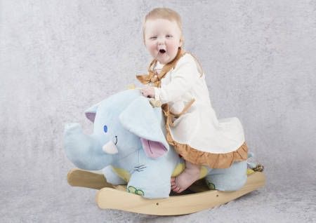 Baby on a rocking horse Stock Photo