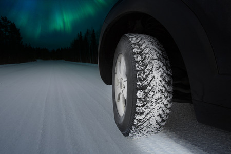 winter tires: Good winter tires on snowy road - Northern lights