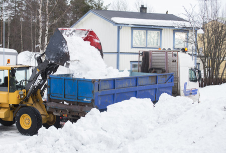 loader: Wheel loader unloading snow Stock Photo