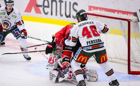 Lulea, Sweden - March 18, 2015. Christoffer Persson (#46 Frolunda Indians) cross-checks Lennart Petrell in front of the net. Swedish Hockey League-game, between Lulea Hockey and Frolunda Indians.