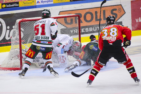 opponents: Lulea, Sweden - March 18, 2015. Karl Fabricius  (#52 Lulea Hockey) slides with full speed into opponents goalie. Swedish Hockey League-game, between Lulea Hockey and Frolunda Indians.