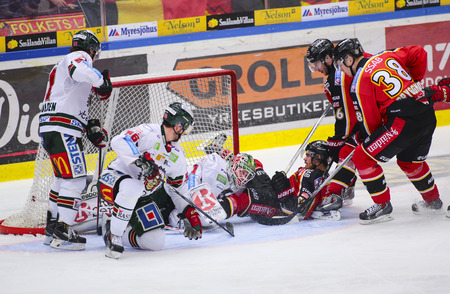 karl: Lulea, Sweden - March 18, 2015. Karl Fabricius  (#52 Lulea Hockey) slides with full speed into opponents goalie. Swedish Hockey League-game, between Lulea Hockey and Frolunda Indians.
