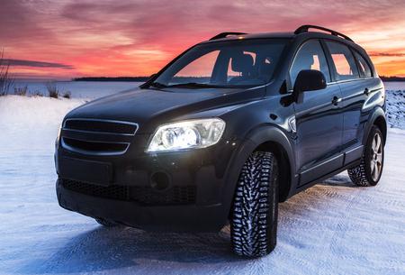 SUV met zonsondergang achtergrond winter landschap Stockfoto - 71923092