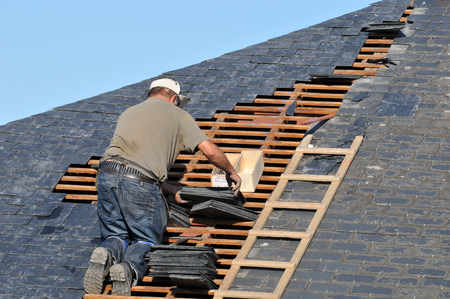 Roofer posing slate on a roof Stock Photo