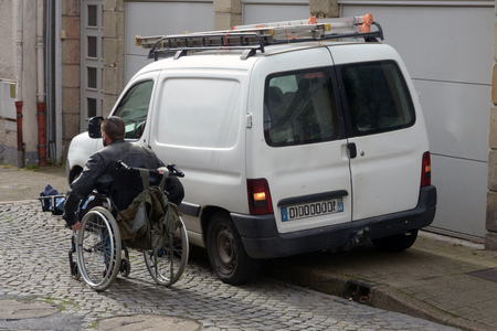 Handicapped person injured by a car parked poorly Stock Photo