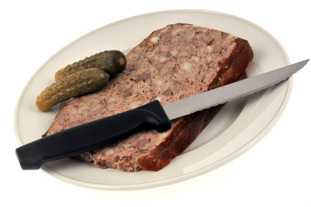 Slice of pate on a plate with pickles
