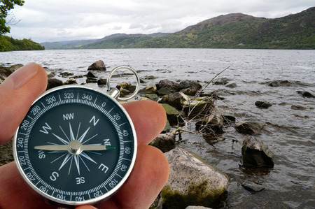Compass in hand in front of a lake