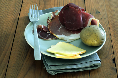 Potatoes, raw ham and cheese on a plate