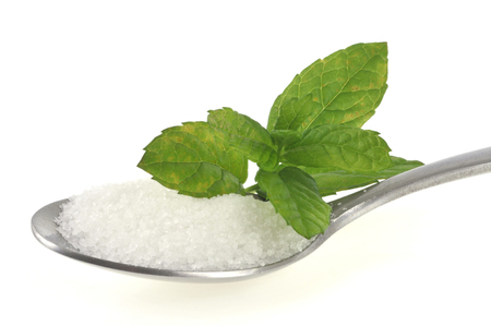 Spoon of powdered sugar with stevia leaves
