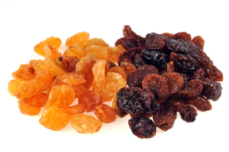 Blond raisins and black raisins on a white background