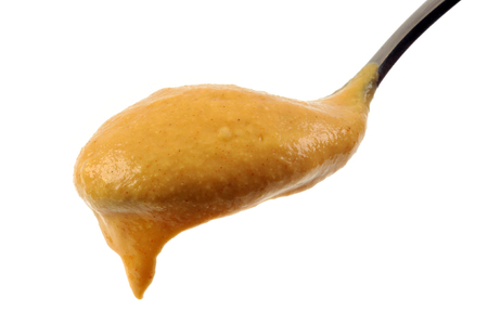 A spoon of mustard on a white background
