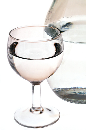 Glass and carafe of water in closeup on white background Stok Fotoğraf