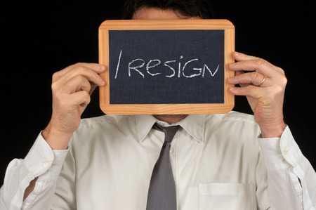 Man hiding his face with a slate on which is written I resign