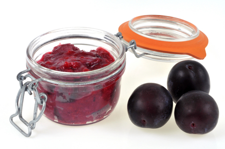 Plum jam in a jar on a white background