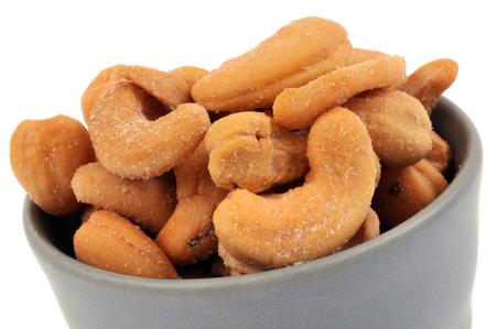 Pecan nuts in a ramekin on a white background