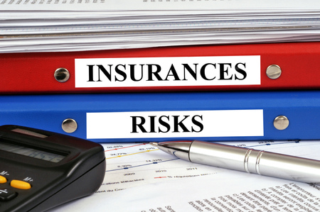 Insurance and risk files stacked on a desk Stock Photo