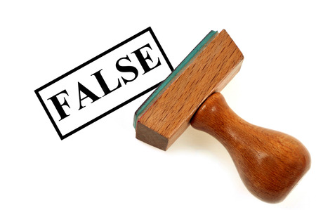 Wooden stamp indicating false on a white background