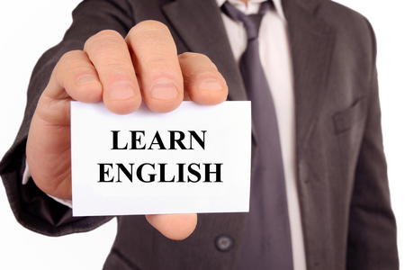 Man holding a card on which is written learn English