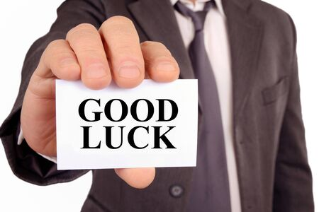 Man holding a card with a good luck written on it