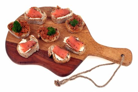 Tapas on a cutting board on a white background