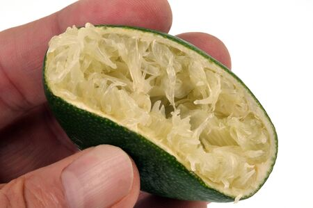 Lime squeezed in hand in closeup Banco de Imagens