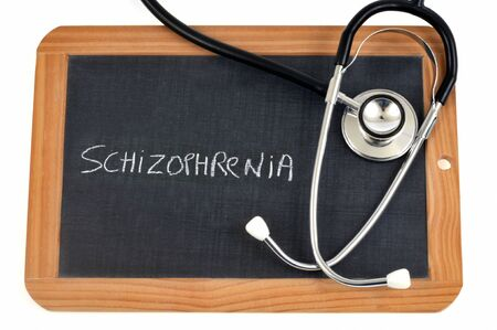 Schizophrenia written on a school slate with a stethoscope Banco de Imagens