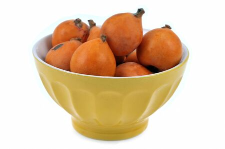 Bowl of loquats in closeup on white background Banco de Imagens
