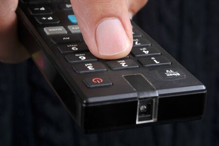 Close-up on a TV remote control in hand
