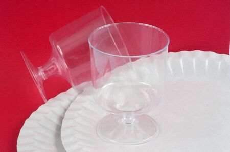 Plastic glasses and cardboard plate on red background
