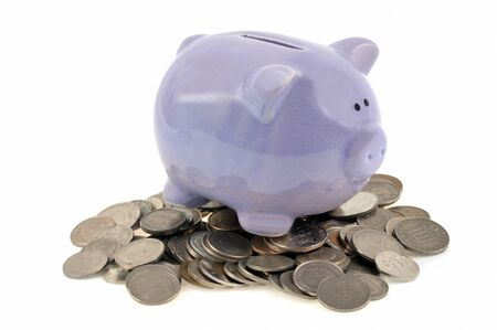 Piggy bank on coins in closeup on white background