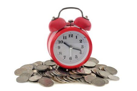 Alarm clock on coins on a white background Stockfoto