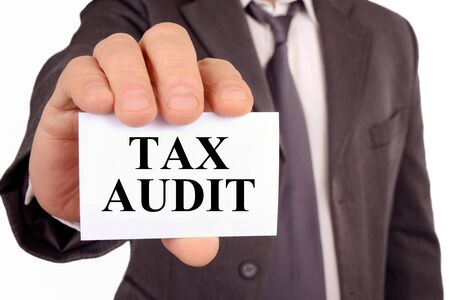 Anonymous man holding a card on which is written tax audit Stok Fotoğraf