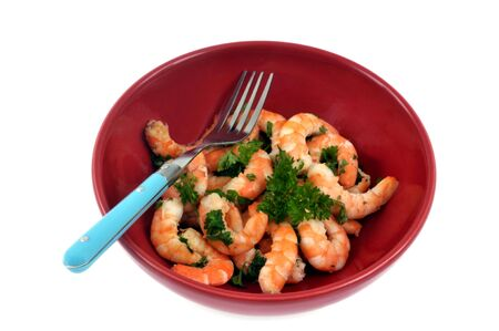 Plate of shrimps with parsley on a white background