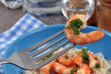 Shrimp with parsley on a fork in close-up