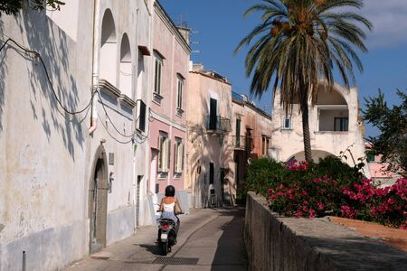 Woman riding a scooter in an alley of Procida Stock Photo