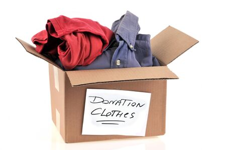 Donation of clothes in a cardboard on a white background