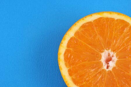 Orange slice in close-up on blue background Stock Photo