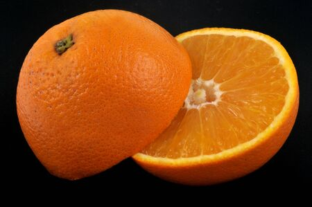 Orange cut in half on a black background