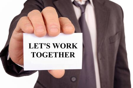 Man holding a card on which is written lets work together