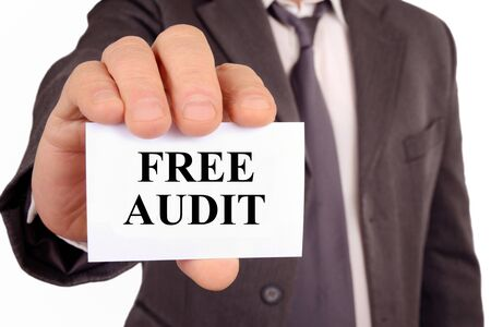Man holding a card on which is written free audit
