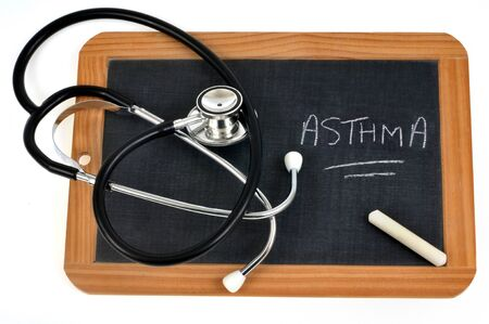 Asthma written on a school slate with a chalk and a stethoscope