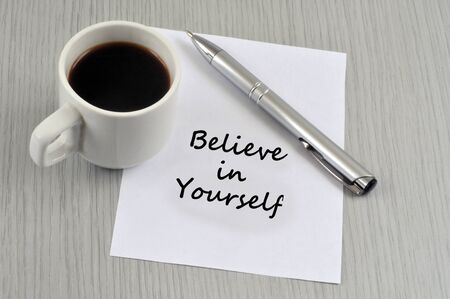 Believe in yourself written on a sheet of paper with a pen next to a cup of coffee Stock Photo