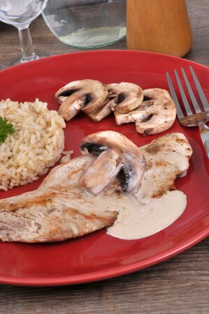 Veal cutlet with rice and mushroom sauce served on a plate